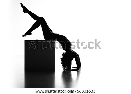 a black and white artistic nude of a woman, shot on white background. she is sitting on a cube, with her hands on the floor, her head down and her legs up in the air. - stock photo