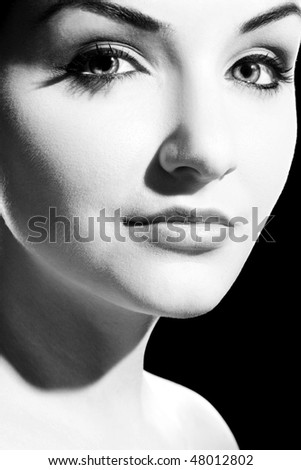 A black and white close up of a beautiful young woman looking at the camera.