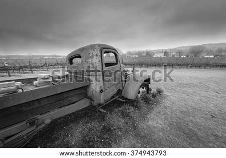 A black and white image of a rusty old truck with bullet holes in the door.
