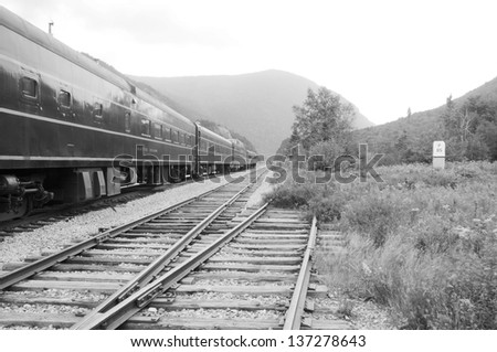 A black and white image of a train parked on the tracks, mountains in the distance