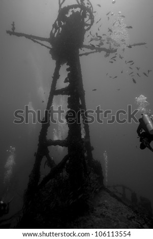 A black and white image of divers swimming around the crows nest of the USCG Duane in Key Largo, Florida. A sunken shipwreck in the John Pennekamp State Park. One female is wearing doubles. - stock photo