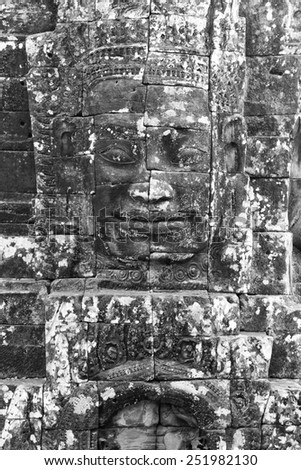 a black and white image of the face of an ancient king carved into stone at a ruin in Cambodia - stock photo