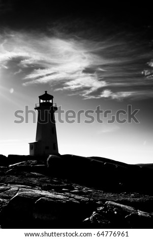 a black and white image of the lighthouse at Peggy's Cove, Nova Scotia, Canada. Image shows rock and cloudy sky - stock photo