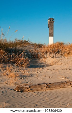 A Black and White Lighthouse on the Beach - stock photo