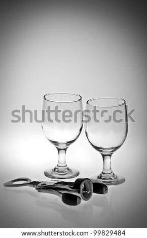 A black and white of empty wine glasses and a corkscrew. - stock photo