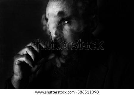 A black and white photo of a handsome man smoking an electronic cigarette on a dark grey background