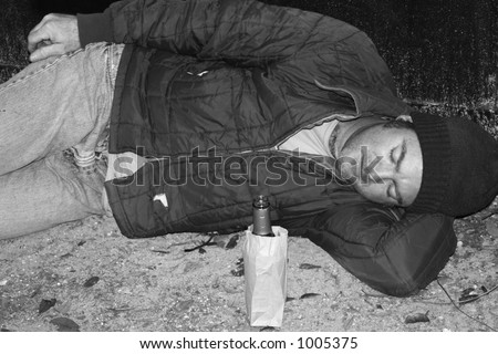 A black and white photo of a homeless man sleeping on the ground by a dumpster.  He has a bottle of wine in a bag beside him. - stock photo