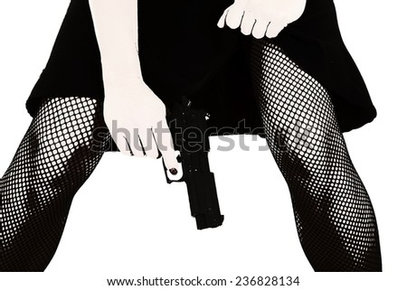 A black and white photo of a woman's legs and she is holding on to her pistol - stock photo