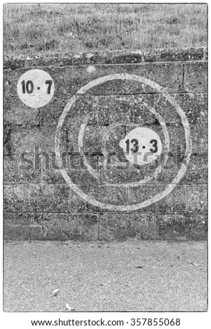 A black and white photo of numbers in a circle painted on dark brickwork wall of an outdoors football field in Europe - stock photo