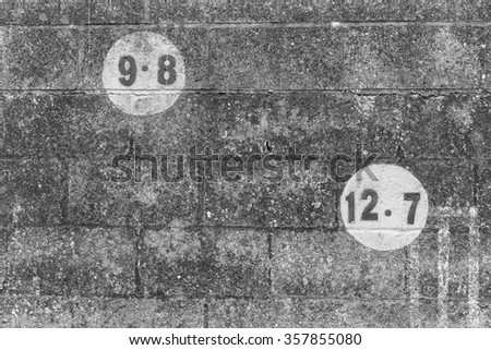 A black and white photo of numbers in a circle painted on dark brickwork wall of an outdoors football field in Europe