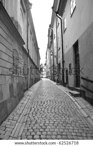 A black and white photo taken down a narrow street - stock photo