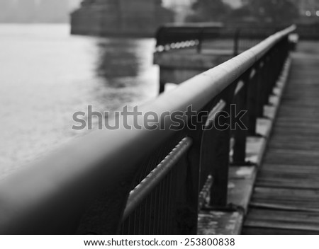 A black and white photograph of a railing on the wooden walking path in Brooklyn Bridge Park that leads to the Manhattan Bridge. - stock photo