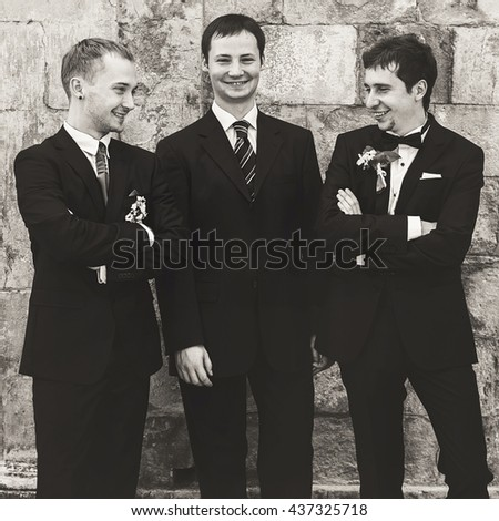A black and white picture of groom posing with his friends