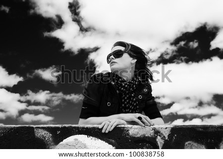 A black and white portrait of a beautiful young woman with wind swept hair, looking off in the distance with a beautiful spring sky behind her. - stock photo