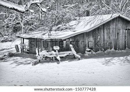 A black and white rural scene photograph of vintage barn on a bright sunny winter morning after a fresh snow fall.