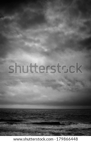 A black and white shot looking out to the Pacific Ocean during a cool winter storm. - stock photo