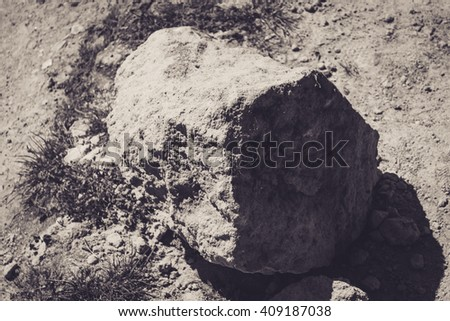 A black and white shot of a big rock on a path full of sand - stock photo