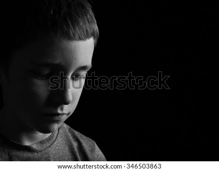 A black and white shot of a boy looking sad
