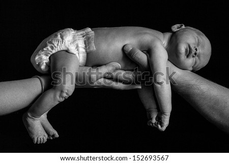 A black and white shot of a newborn baby boy being held up by two hands.