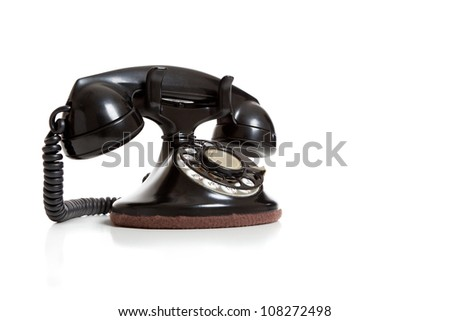A black antique telephone on a white background with copy space - stock photo