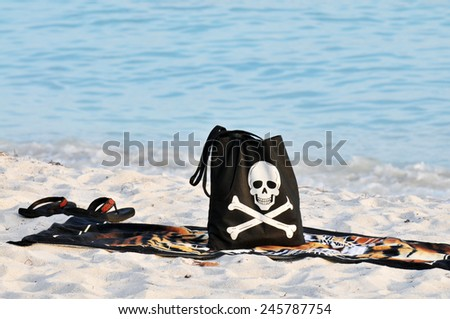 A black beach back with a smiling skull and crossbones with a towel and flip flops  on a sandy beach. - stock photo