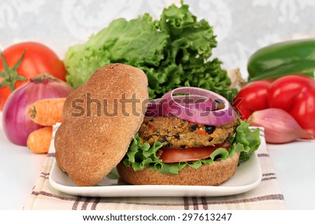 A black bean vegetarian burger on a whole wheat roll with tomato, onion and greens.