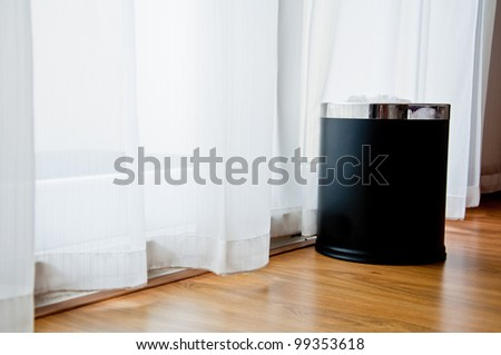 a black bin at the window with white curtain and window lighting - stock photo