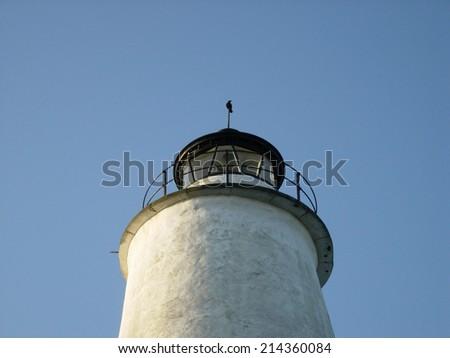 A black bird on top of the Ocracoke Island lighthouse in Ocracoke, North Carolina. - stock photo