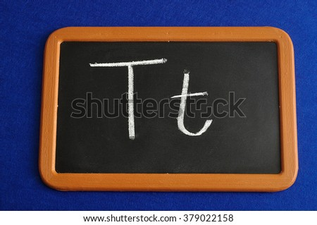 A black board with the alphabet letter T in a capital and small letter isolated on a blue background