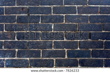 A black brick wall, suitable as a background or texture - stock photo