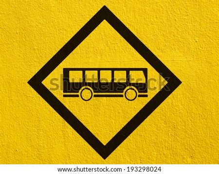 a black Bus Stop Sign painted on a stucco wall outside - stock photo