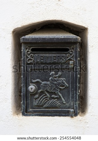 A black cast iron letterbox in a white wall niche with an engraving of a horse and knight and the word LETTERS. - stock photo