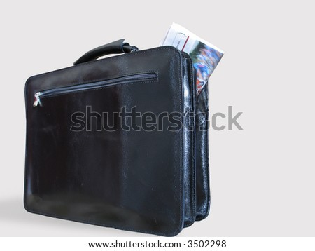 A black casual leather briefcase, and a newspaper partly outside it
