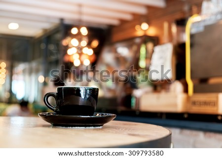 A black cup of coffee in coffee shop. vintage effect. - stock photo