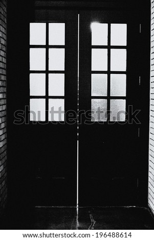 A black door with eight small windows on each side of the door.