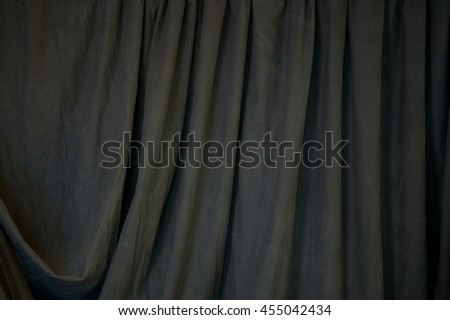 A black draped backdrop cloth fills the image with vertical folds. - stock photo