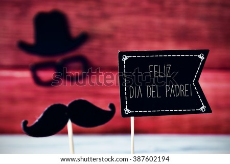 a black flag-shaped signboard with the text feliz dia del padre, happy fathers day in spanish, and a mustache, a pair of eyeglasses and a hat forming the face of a man - stock photo