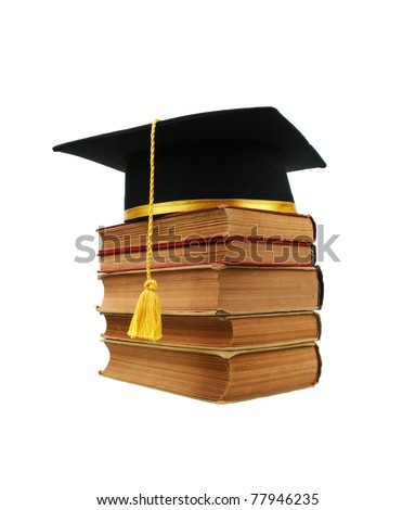 A black graduation cap on top of a stack of old books isolated on a white background