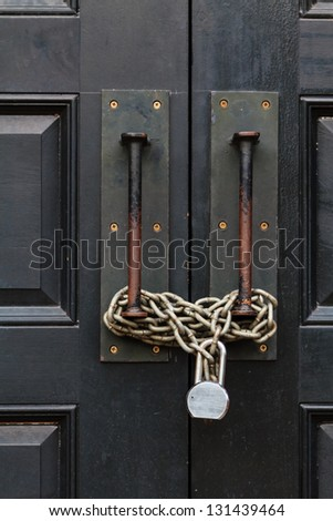 A black large door closed with a chain and a lock - stock photo