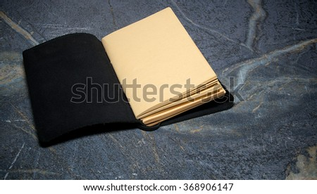 A black leather bound book is open to the first page that is blank on soapstone table top.