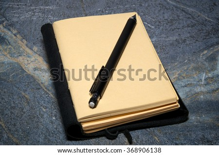 A black leather bound writing journal or artist sketchbook is open to blank page with mechanical pencil resting on page on soapstone surface.