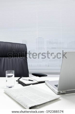 A black leather chair, planner, a laptop and a desk. - stock photo