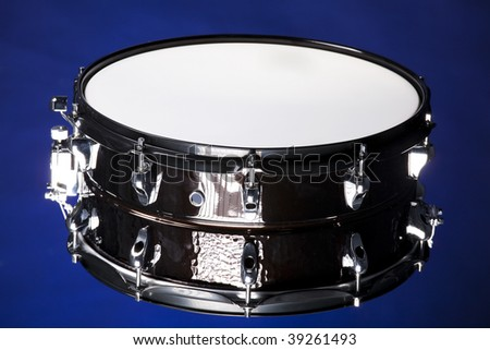A black metallic snare drum isolated against a dark blue background in the horizontal format.