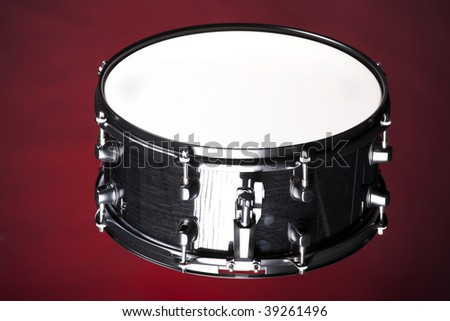 A black metallic wood finish snare drum isolated against a dark red background in the horizontal format.