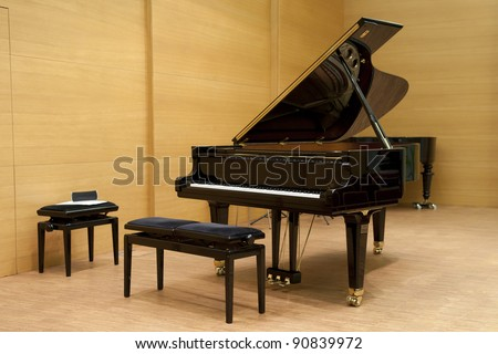 a black piano ready for playing with stool in front on a wooden stage - stock photo