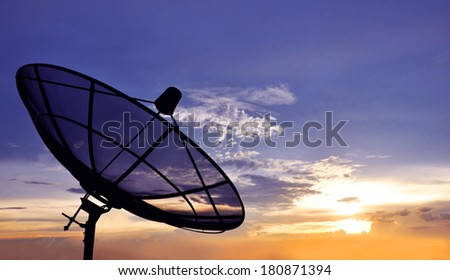 A black satellite dish on twilight sky background - stock photo