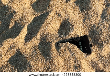 A black smart phone left buried in the send on a beach with the boss calling. - stock photo