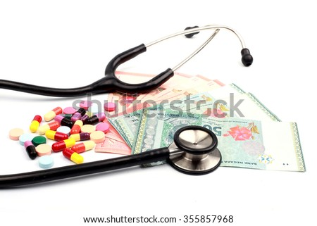 a black stethoscope and colorful pills on various Malaysian currency closed up - stock photo