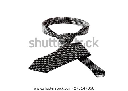 A black tie with small white dots, with a tie knot done, on an isolated white background. - stock photo