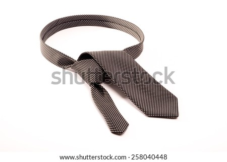 A black tie with white dots on a white background folded as if to make a tie knot around the neck. - stock photo